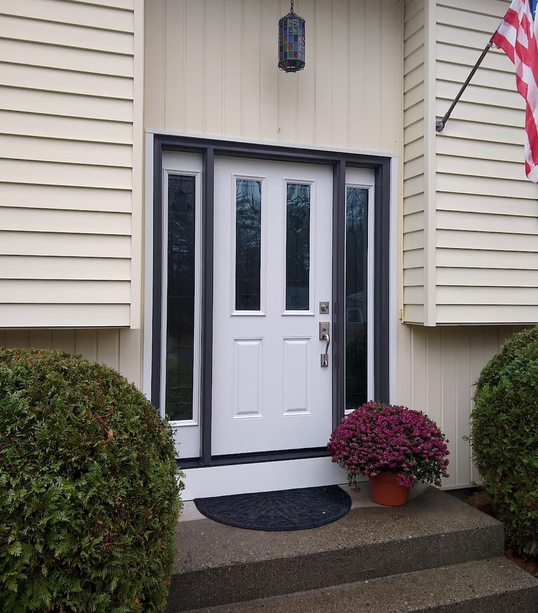 Exterior view of new white fiberglass entry door and vinyl window sidelights.
