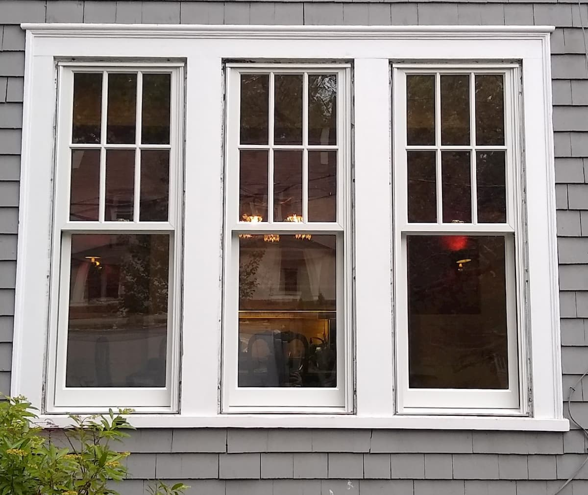 Exterior view of three white wood double-hung windows.