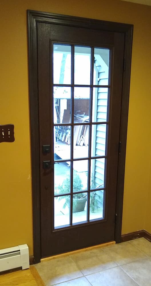 Interior view of new wood entry door with traditional grille pattern on glass
