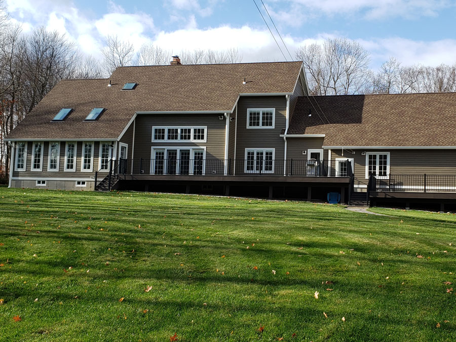 Back exterior view of West Granby, CT, home with new wood windows and a wood patio door