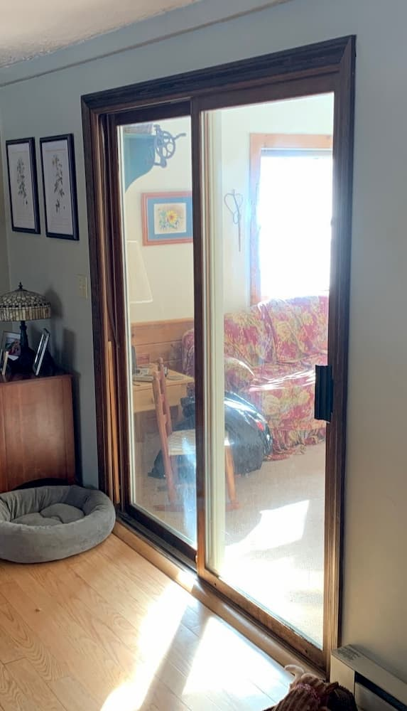 Wood sliding glass door opening onto a sun room