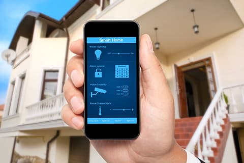 Hand holding mobile device with smart home application active
