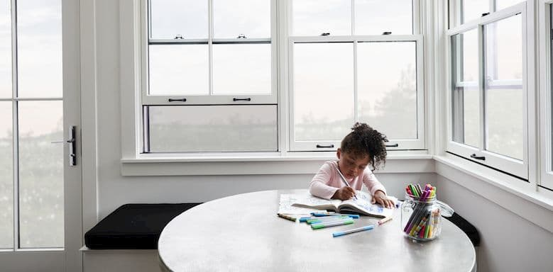 Little girl sitting at a table coloring in a room with white double-hung windows