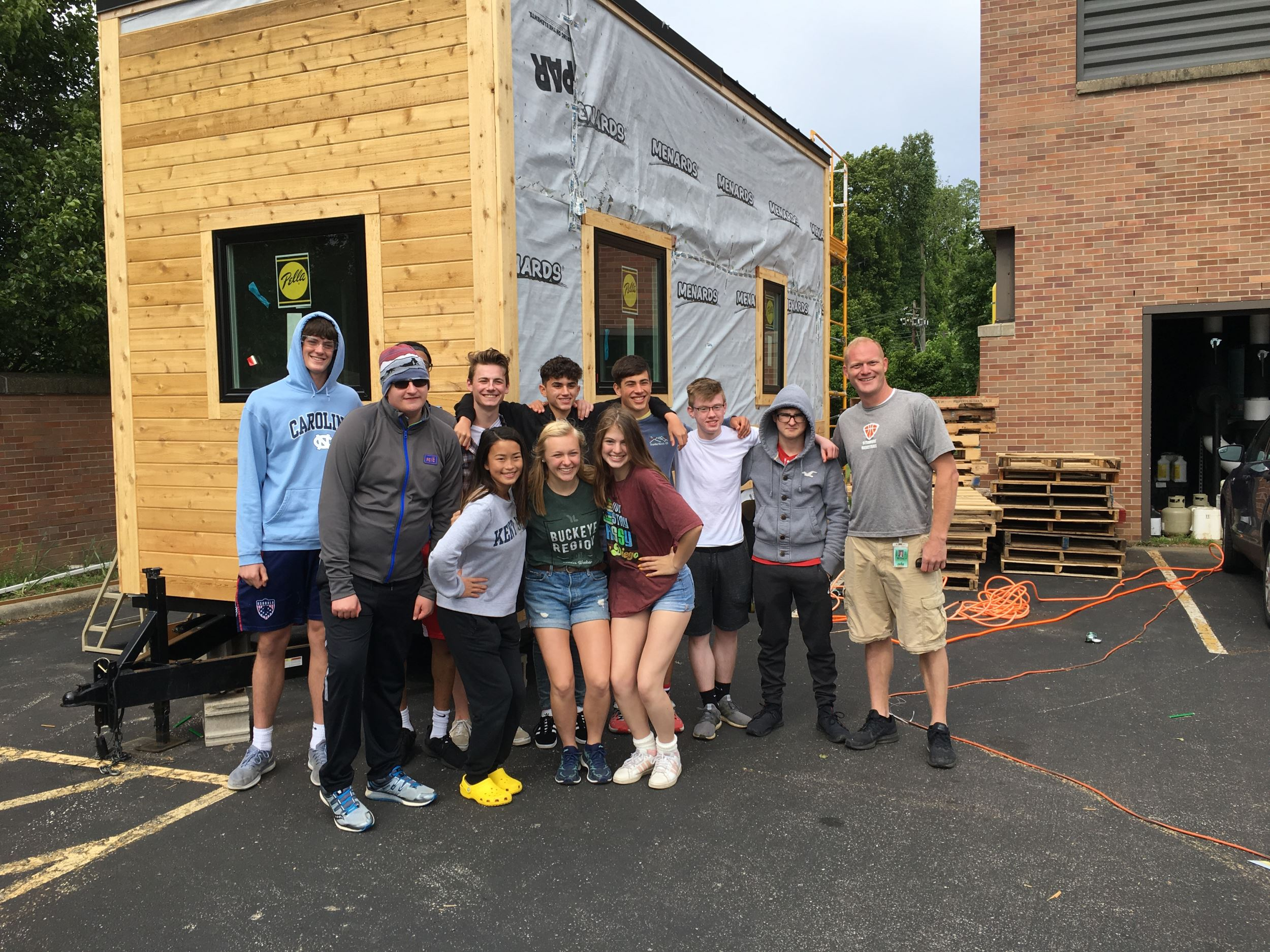 High school students posing outside a tiny house they built with Pella windows